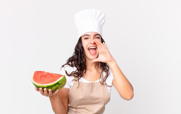 Mulher bonita chef hispânica feliz, dando um grande grito com as mãos perto da boca e segurando uma melancia