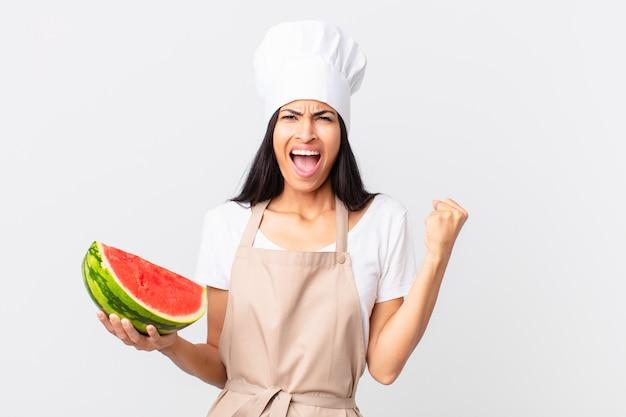 Mulher bonita chef hispânica gritando agressivamente com uma expressão de raiva e segurando uma melancia