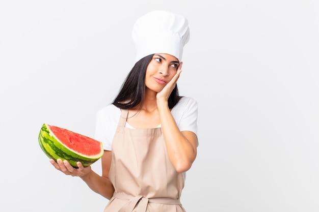 Mulher bonita chef hispânica se sentindo entediada, frustrada e com sono depois de um cansativo e segurando uma melancia