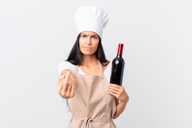 Mulher bonita chef hispânica se sentindo irritada, irritada, rebelde e agressiva e segurando uma garrafa de vinho
