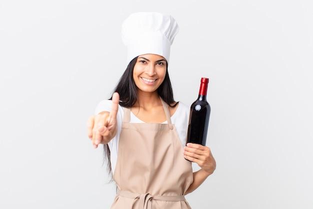 Mulher bonita chef hispânica sorrindo com orgulho e confiança fazendo o número um e segurando uma garrafa de vinho