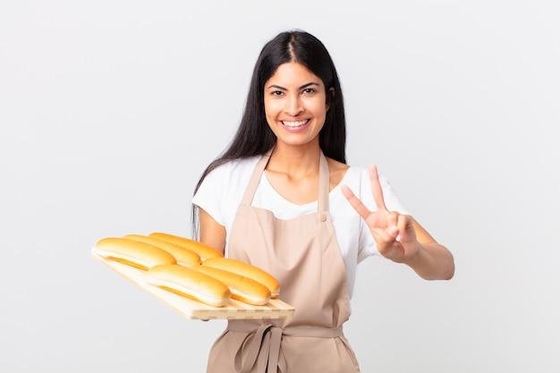 Mulher bonita chef hispânica sorrindo e parecendo feliz, gesticulando vitória ou paz e segurando uma bandeja com pães