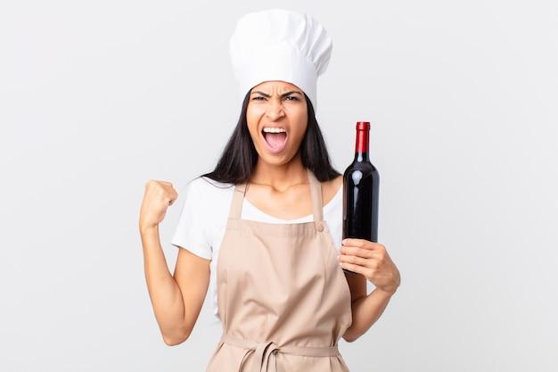 Mulher bonita chefe hispânica gritando agressivamente com uma expressão de raiva e segurando uma garrafa de vinho