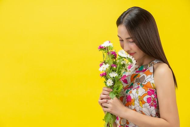 Mulher bonita, cheirando a flor branca