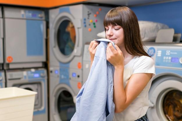 Mulher bonita, cheirando a roupa limpa