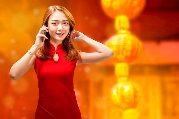 Mulher bonita chinesa com cheongsam vestido falando ao telefone
