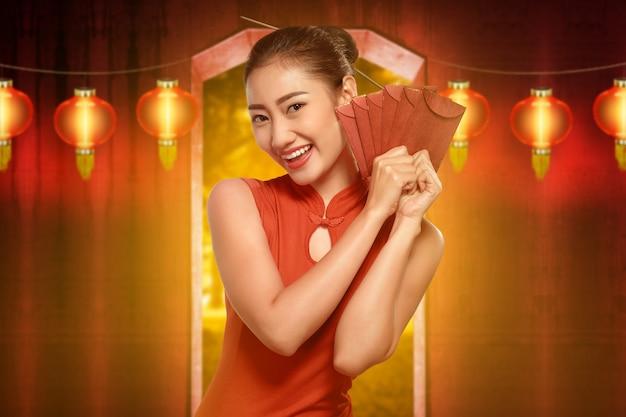 Mulher bonita chinesa com vestido cheongsam segurando envelopes vermelhos