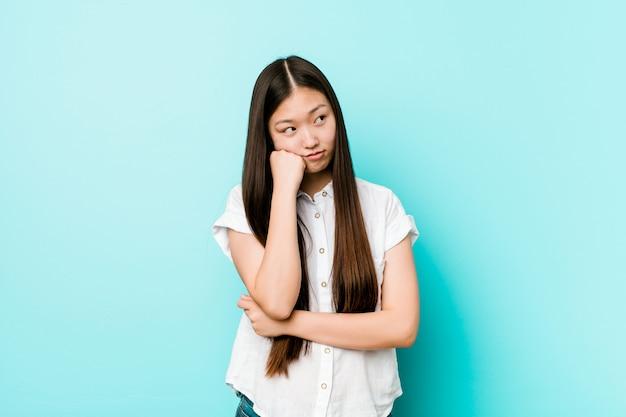 Mulher bonita chinesa jovem que se sente triste e pensativa, olhando para o espaço da cópia.