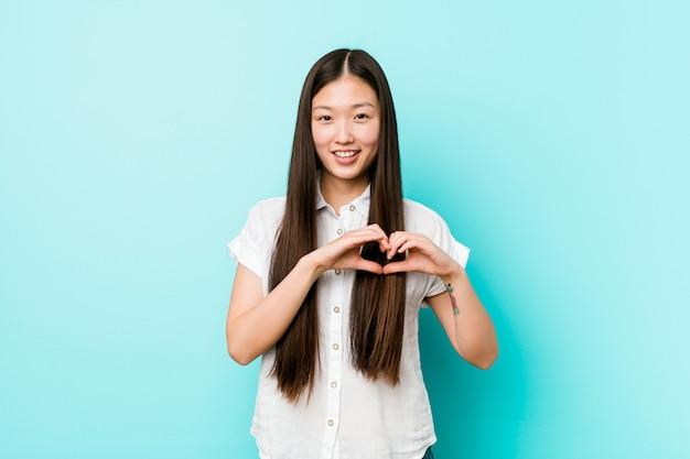 Mulher bonita chinesa jovem sorrindo e mostrando uma forma de coração com as mãos.
