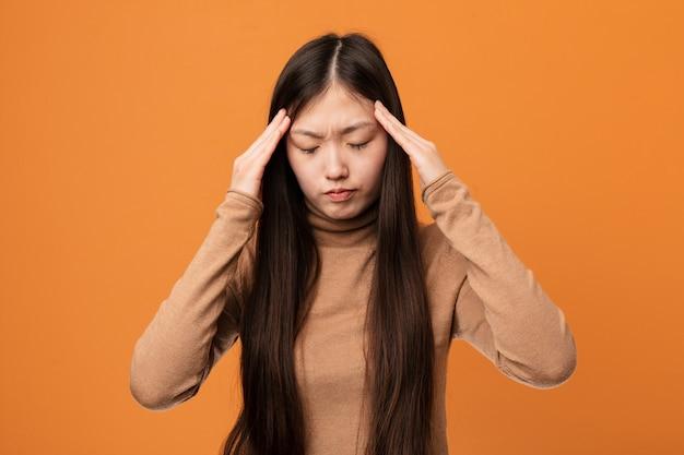 Mulher bonita chinesa jovem tocando os templos e tendo dor de cabeça.