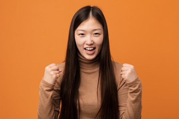 Mulher bonita chinesa jovem torcendo despreocupado e animado.