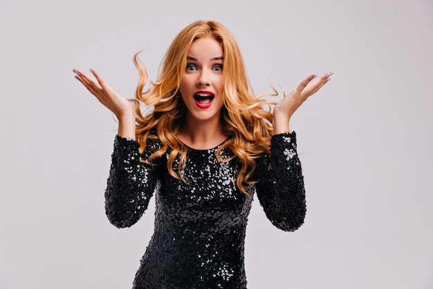 Mulher bonita chocada com cabelo comprido em pé na parede branca. foto interna de uma senhora muito surpresa usa um vestido preto brilhante.