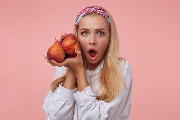 Mulher bonita chocada com camisa branca e xale colorido em pé com pêssegos nas mãos, parecendo assustada com olhos grandes