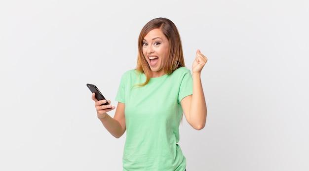 Mulher bonita chocada, rindo e comemorando o sucesso e usando um smartphone