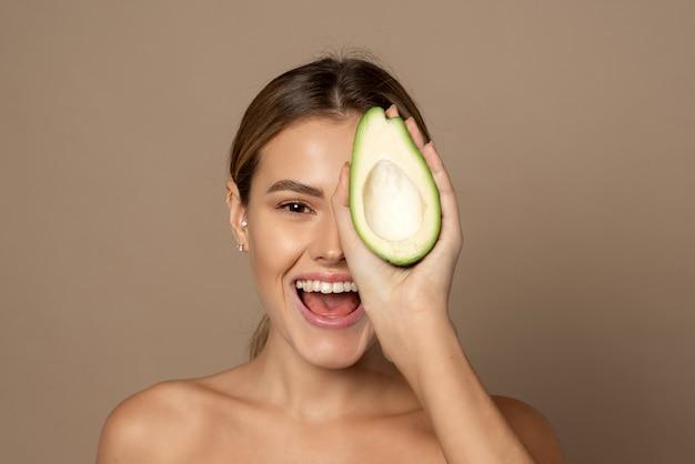 Mulher bonita cobre metade do rosto com metade de um abacate. conceito de beleza e cuidados com a pele.