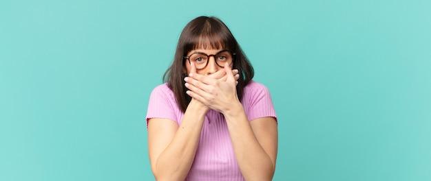 Mulher bonita cobrindo a boca com as mãos com uma expressão chocada e surpresa, mantendo um segredo ou dizendo oops