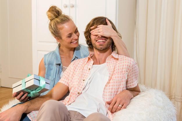 Mulher bonita, cobrindo os olhos do namorado e oferecendo-lhe presentes na sala de estar