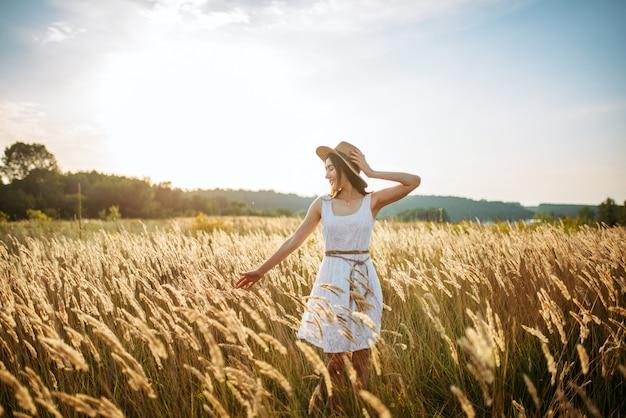 Mulher bonita colhe trigo no campo