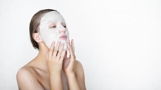 Mulher bonita coloca uma máscara cosmética no rosto