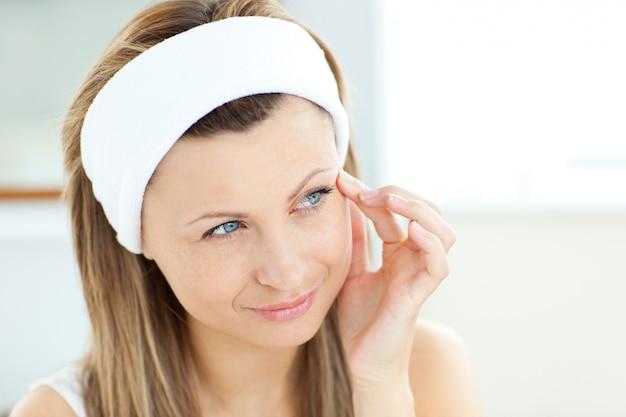 Mulher bonita colocando creme no rosto usando uma bandana no banheiro