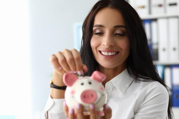 Mulher bonita, colocando dinheiro no moneybank