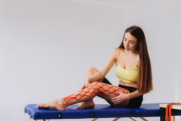 Mulher bonita, colocando fita elástica kinesio no joelho e perna.