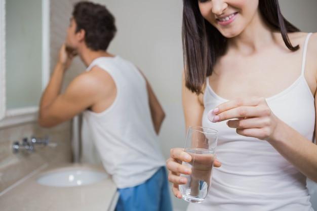 Mulher bonita, colocando o comprimido em um copo de água e o homem olhando no espelho