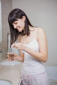 Mulher bonita, colocando o comprimido em um copo de água no banheiro