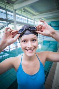 Mulher bonita colocando óculos de natação na piscina
