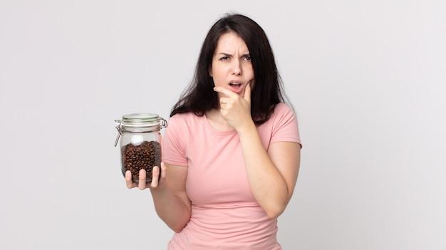 Mulher bonita com a boca e os olhos bem abertos, a mão no queixo e segurando uma garrafa de grãos de café