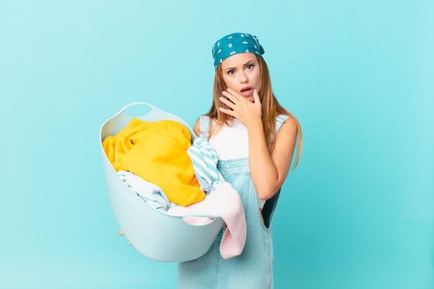Mulher bonita com a boca e os olhos bem abertos e a mão no queixo segurando um cesto de roupa suja