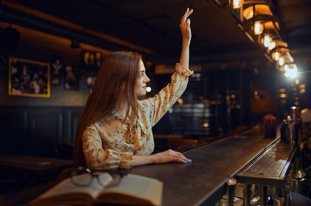 Mulher bonita com a mão levantada, sentado no balcão do bar. uma pessoa feminina em um bar, emoções humanas, atividades de lazer, vida noturna