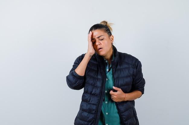 Mulher bonita com a mão na têmpora, colocando a mão na jaqueta na camisa verde, jaqueta preta e parecendo apressada, vista frontal.