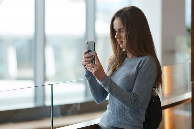 Mulher bonita com a mochila na varanda fazendo foto com seu smartphone através da janela