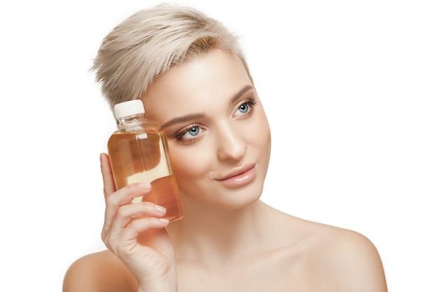 Mulher bonita com a pele perfeita segurando uma garrafa de óleo no estúdio