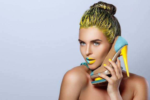 Mulher bonita com amarelo segurando sapatos coloridos