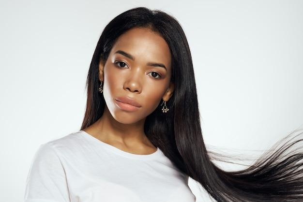 Mulher bonita com aparência africana e brincos de alisamento de cabelo joias