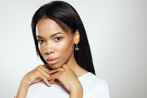 Mulher bonita com aparência africana em camiseta branca, brincos e cabelo comprido