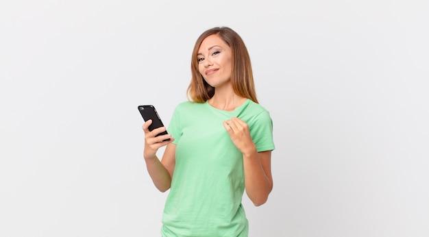 Mulher bonita com aparência arrogante, bem-sucedida, positiva e orgulhosa usando um smartphone