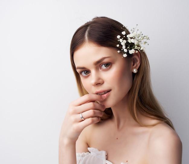 Mulher bonita com aparência atraente e flores no cabelo com fundo claro