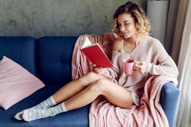 Mulher bonita com aproveitando a manhã ensolarada em casa, segurando o livro favorito, bebendo café. clima aconchegante e caloroso. cores suaves rosa.