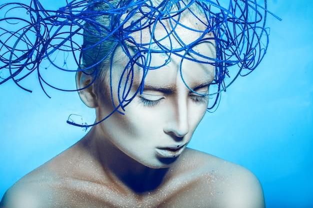 Mulher bonita com arte corporal e olhos fechados em fundo preto azul