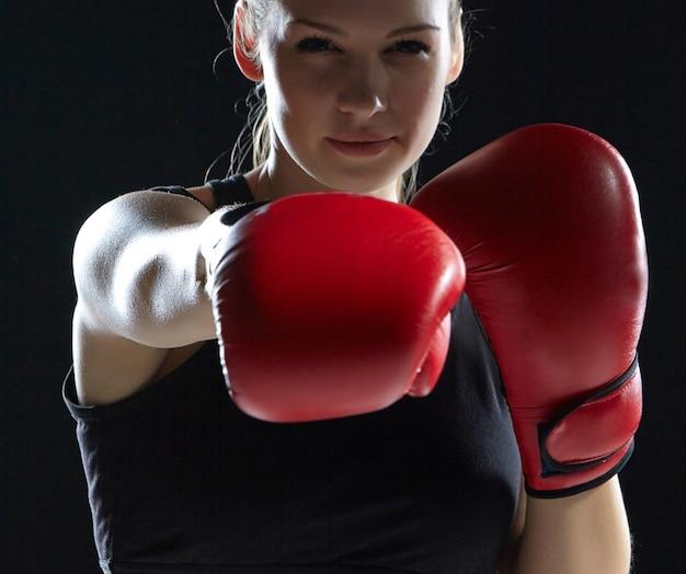 Mulher bonita com as luvas vermelhas é boxe em fundo preto