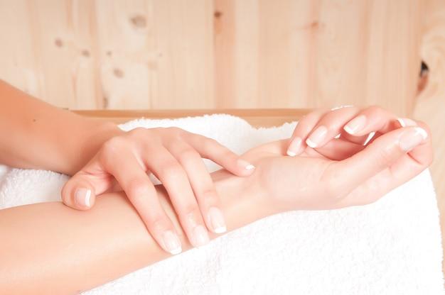 Mulher bonita com as mãos no spa