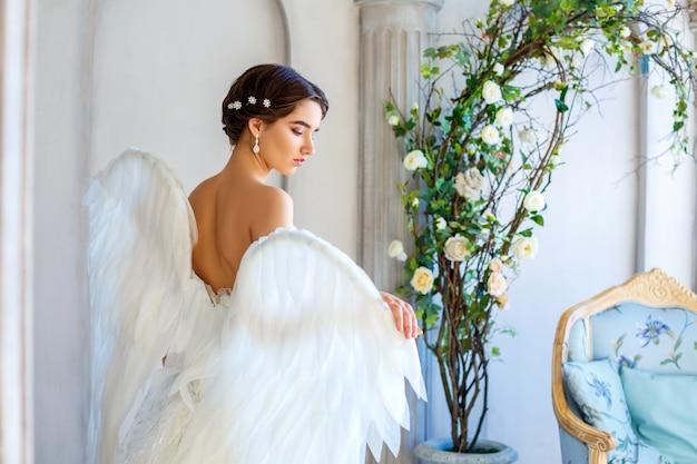 Mulher bonita com asas de anjo inspira beleza