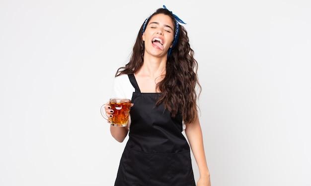 Mulher bonita com atitude alegre e rebelde, brincando e mostrando a língua e segurando um copo de cerveja