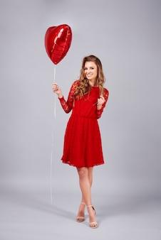 Mulher bonita com balão em forma de coração.