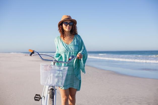 Mulher bonita com bicicleta andando na praia ao sol