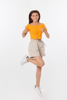 Mulher bonita com blusa laranja, pulando e mostrando os polegares