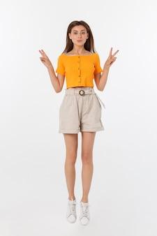 Mulher bonita com blusa laranja pulando